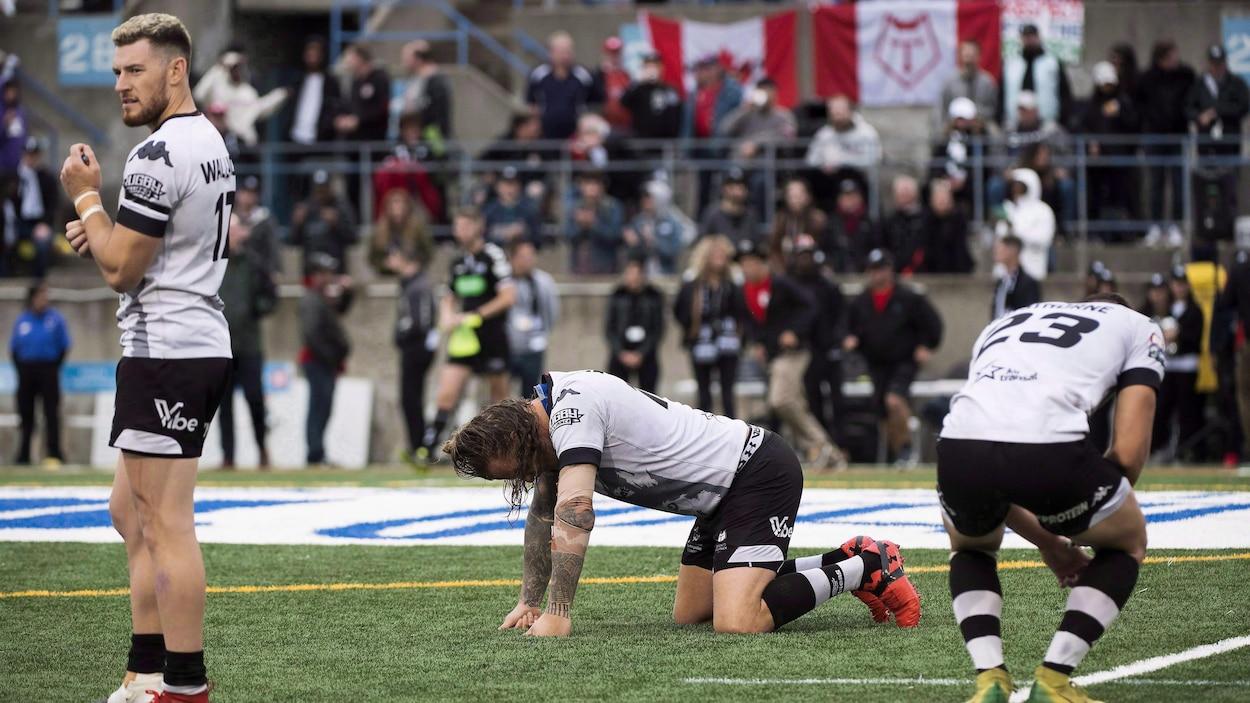 Des joueurs de rugby réagissent à une défaite au coup de sifflet final.
