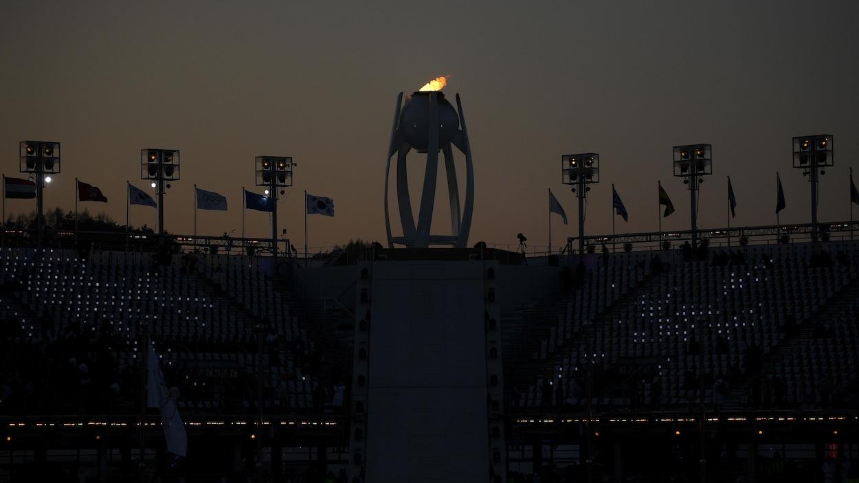 La flamme olympique brille dans le ciel obscurci.