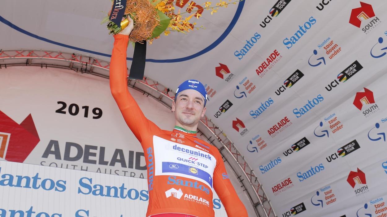 Il salue la foule, bouquet de fleurs à la main droite, au terme d'une première journée couronnée de succès au Tour Down Under.
