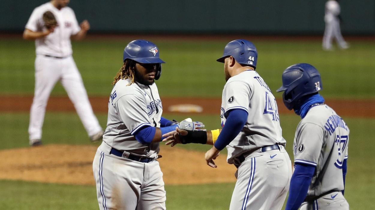 Trois coéquipiers se félicitent après qu'un d'eux eut marqué un point dans un match de baseball.