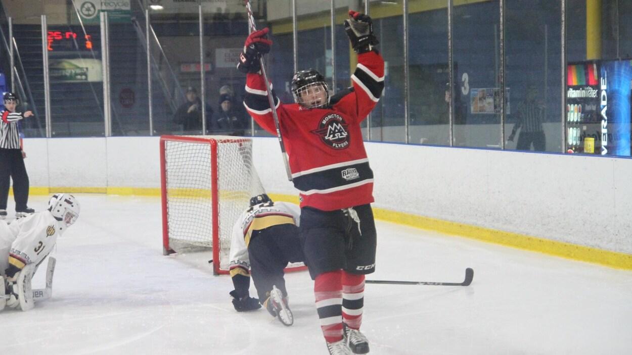 Un joueur de hockey qui lève les bras en l'air après avoir marqué un but.
