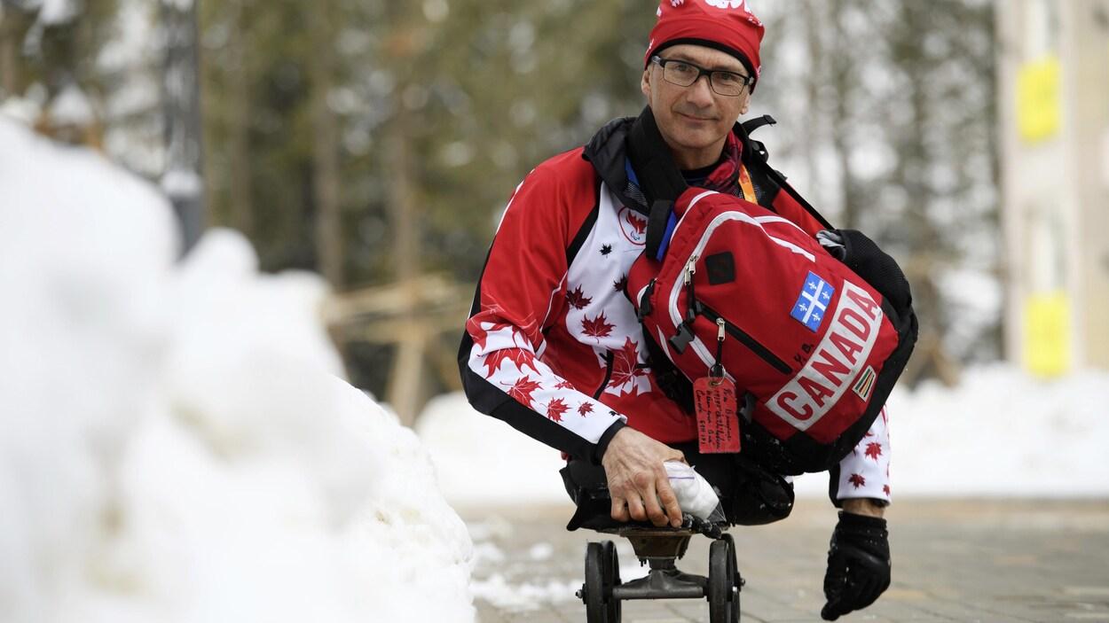 Yves Bourque sourit à la caméra. Il est en train de se déplacer sur sa planche à roulettes. Il porte un sac à dos aux couleurs du Canada.