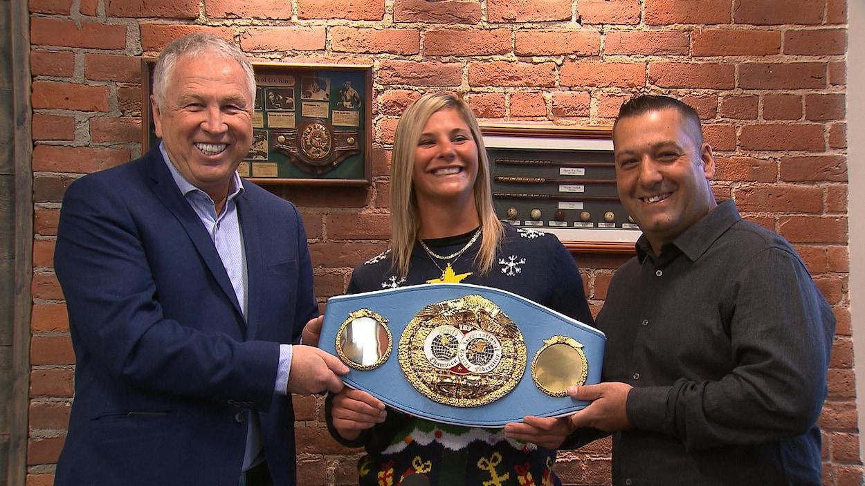 Elle tient sa ceinture entre les deux hommes.