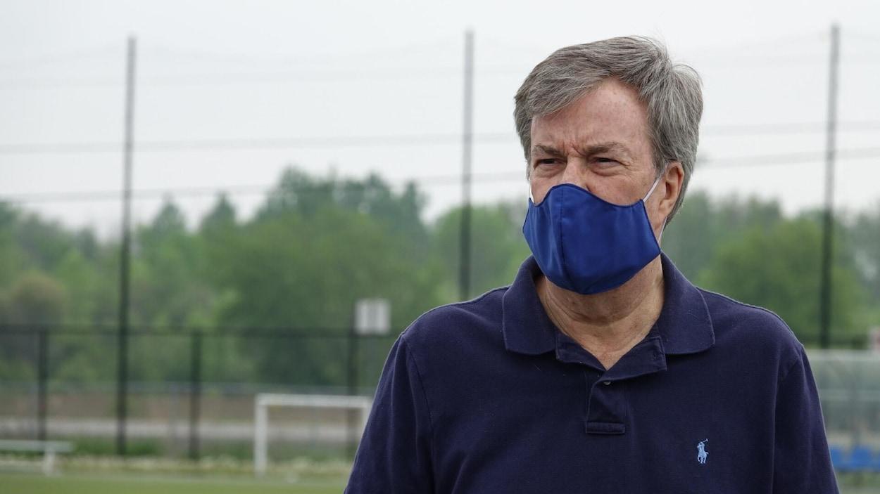 Le maire portant le masque, sur le terrain de soccer.