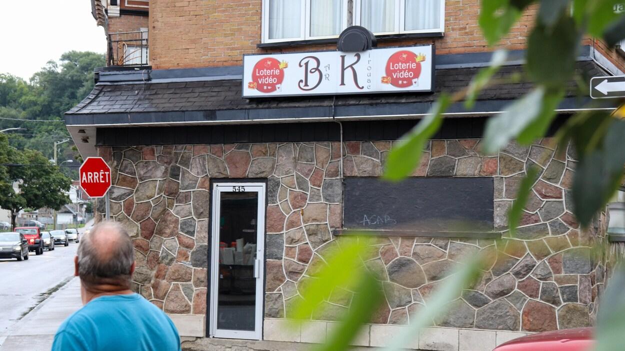 Un homme passe devant le Bar le Kirouac.