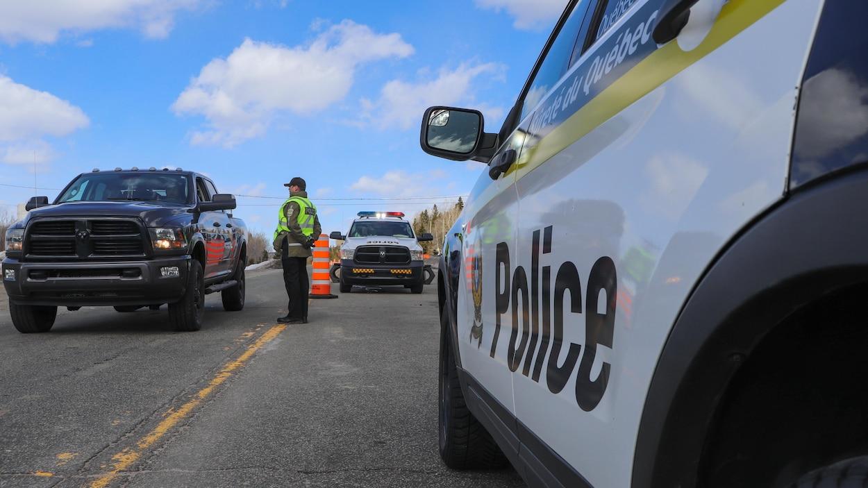 Des policiers discutent avec des automobilistes sur une route