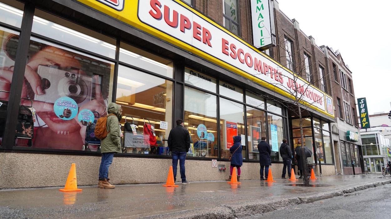 Des gens font la file devant une pharmacie sur l'avenue du Mont-Royal, à Montréal.