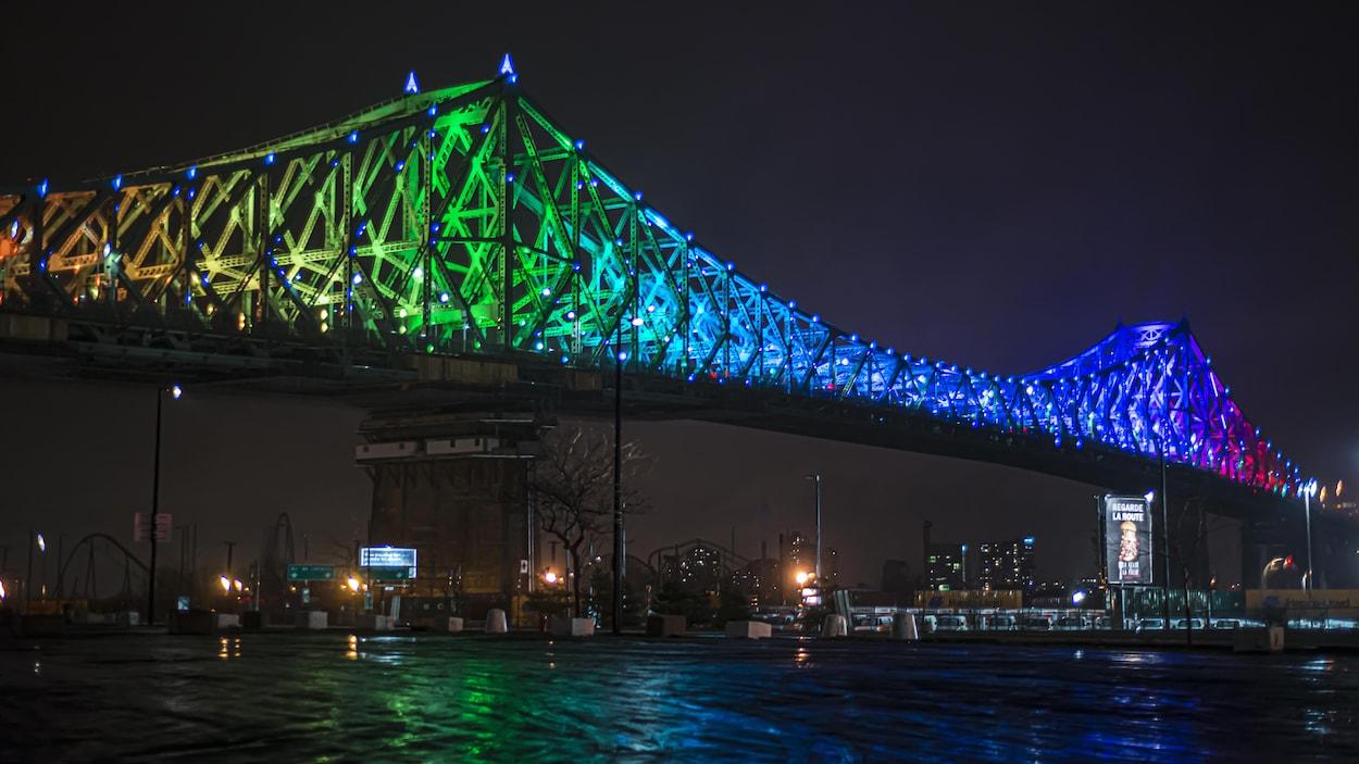 De nuit, les couleurs se reflètent dans l'eau du fleuve.