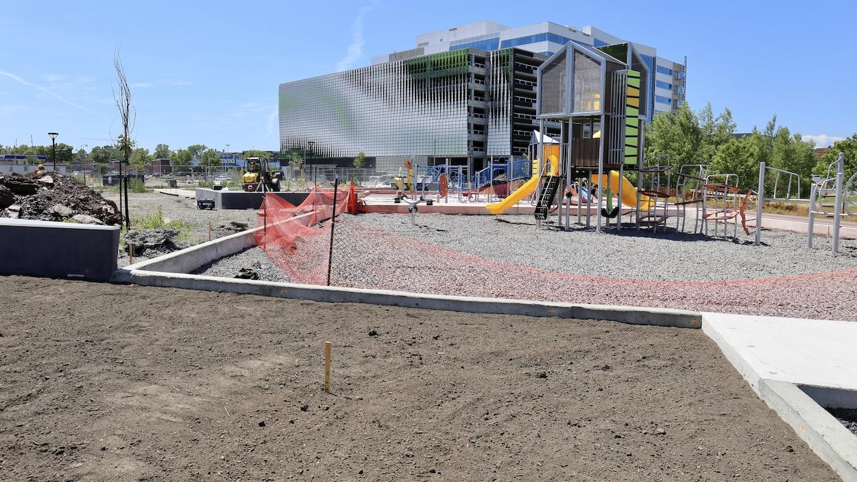 À l'arrière-plan : un immeuble en construction... devant : un module de jeux pour enfant fraîchement installé.