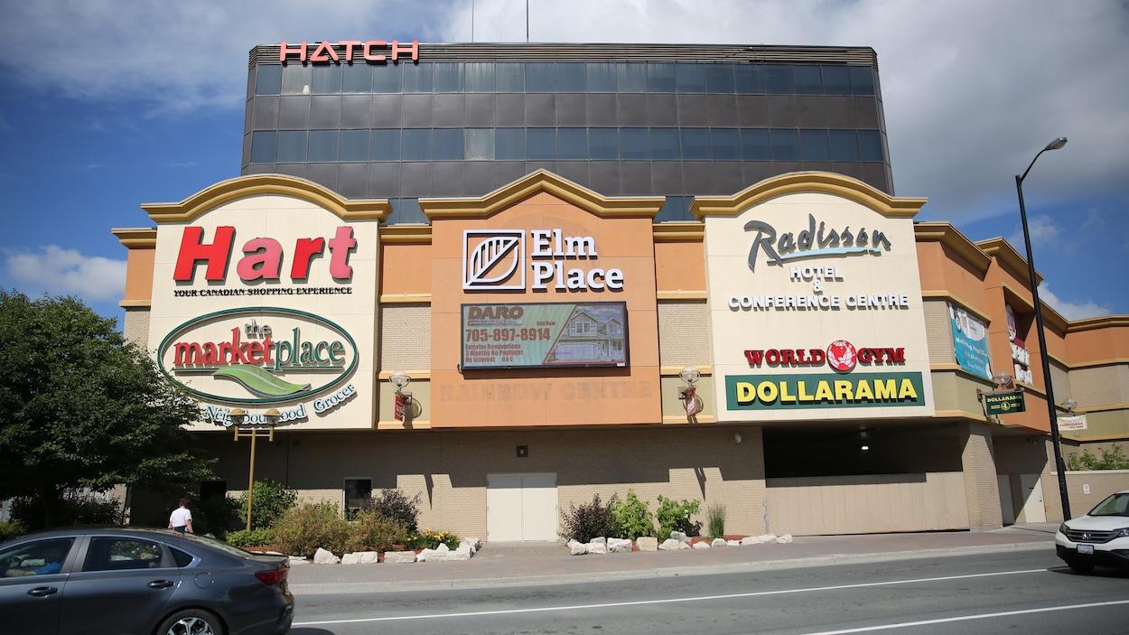 Les nouveaux nom et logo du centre commercial sont visibles aux côtés d'autre enseignes des commerces locataires du centre commercial.