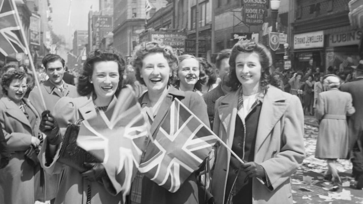 Trois jeunes femmes dans la foule qui célèbre le jour de la Victoire dans la rue Sainte-Catherine, à Montréal. Cette manifestation populaire souligne la capitulation allemande et la fin imminente de la Seconde Guerre mondiale.