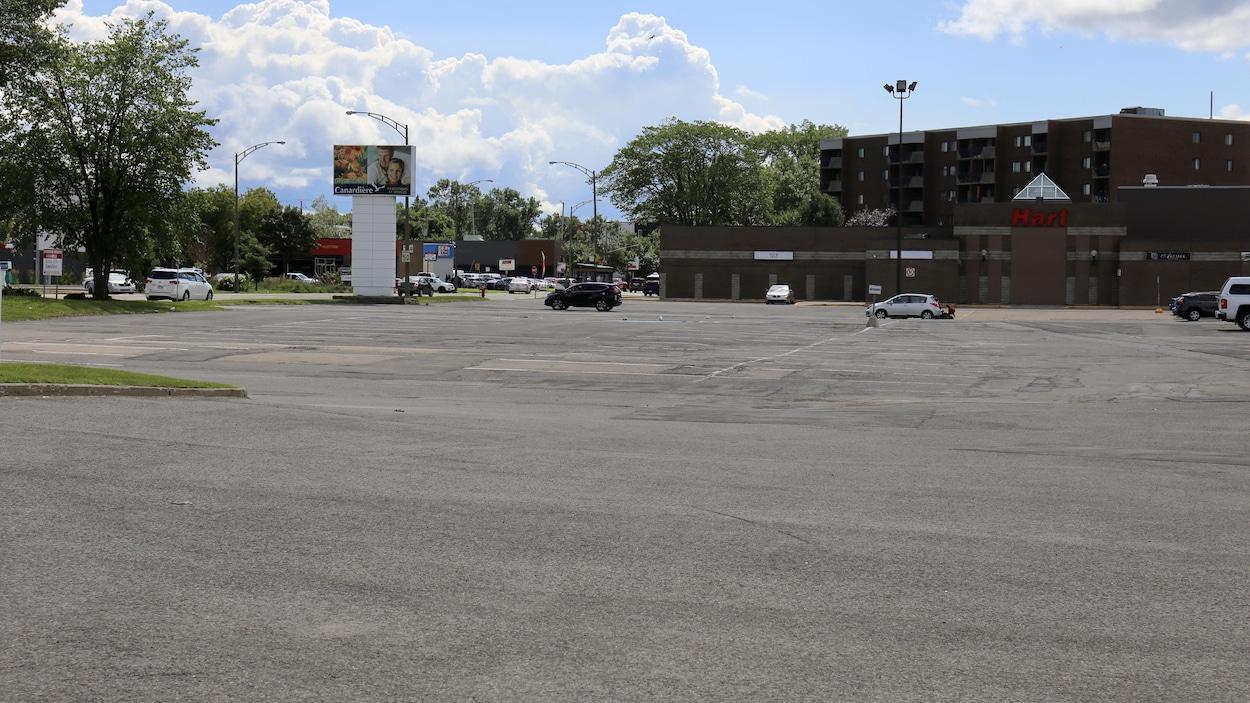 Un plan large d'un petit centre commercial, avec un grand stationnement presque vide
