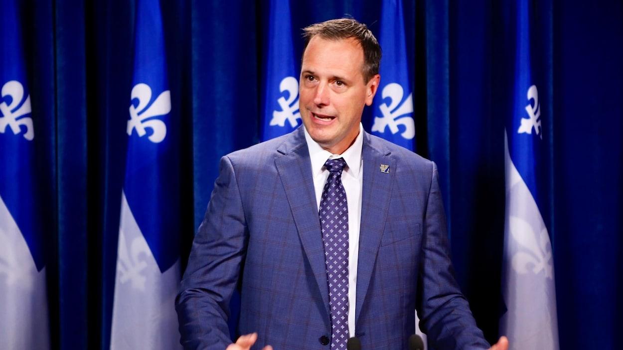 Jean-François Roberge en conférence de presse devant plusieurs drapeaux du Québec.