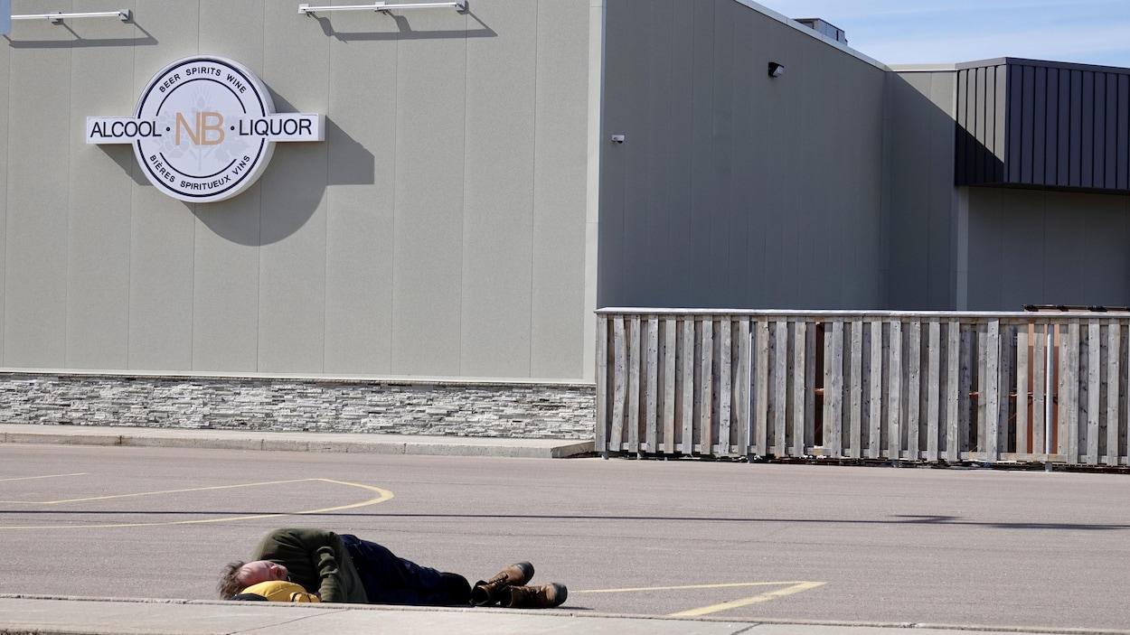 Un homme dort couché sur l'asphalte d'un terrain de stationnement.