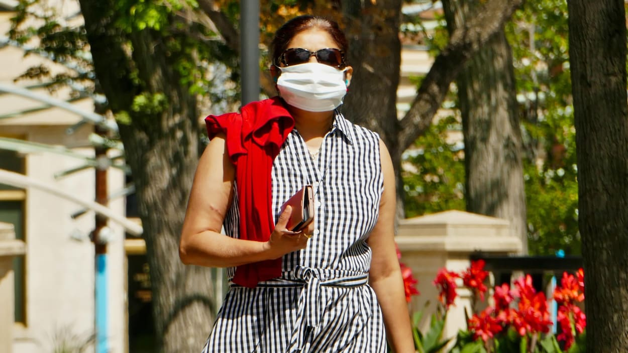 Une femme marche dans la rue avec un masque.