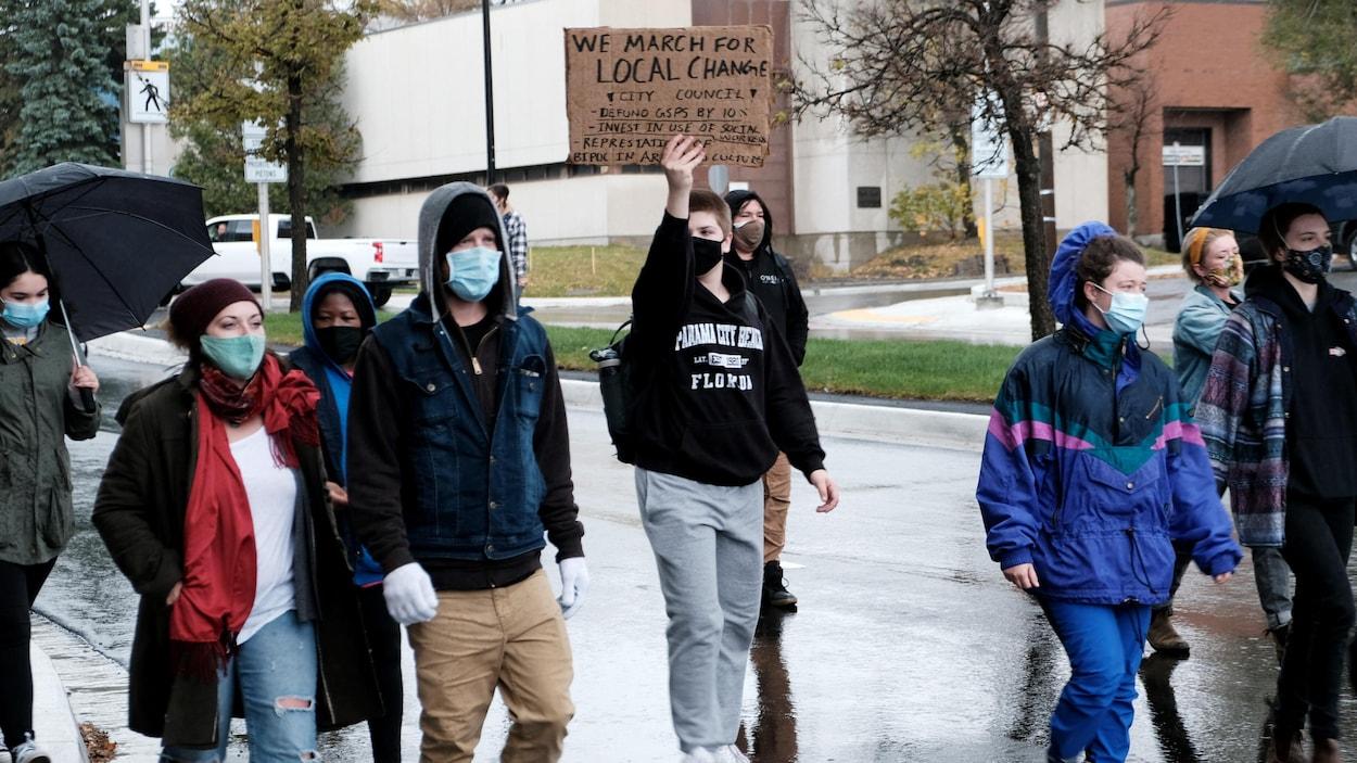 Des manifestants marchent dans la rue en tendant des affiches