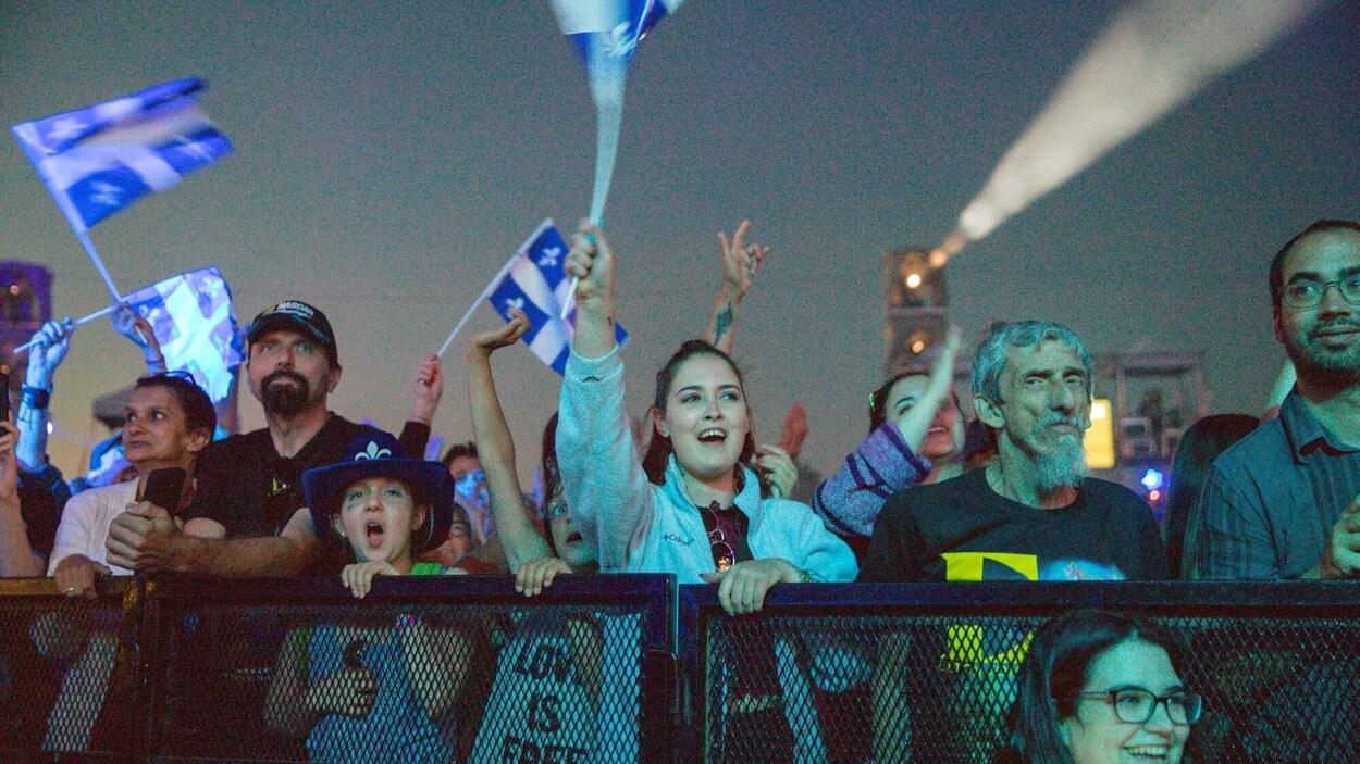 Des gens assistent à un spectacle et agitent des drapeaux du Québec.