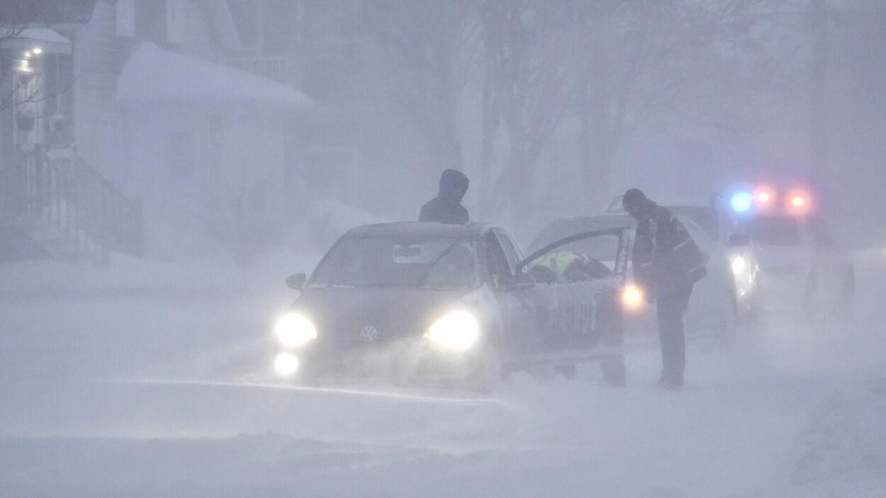 Des policiers viennent en aide à un automobiliste en difficulté sur une rue recouverte de neige.