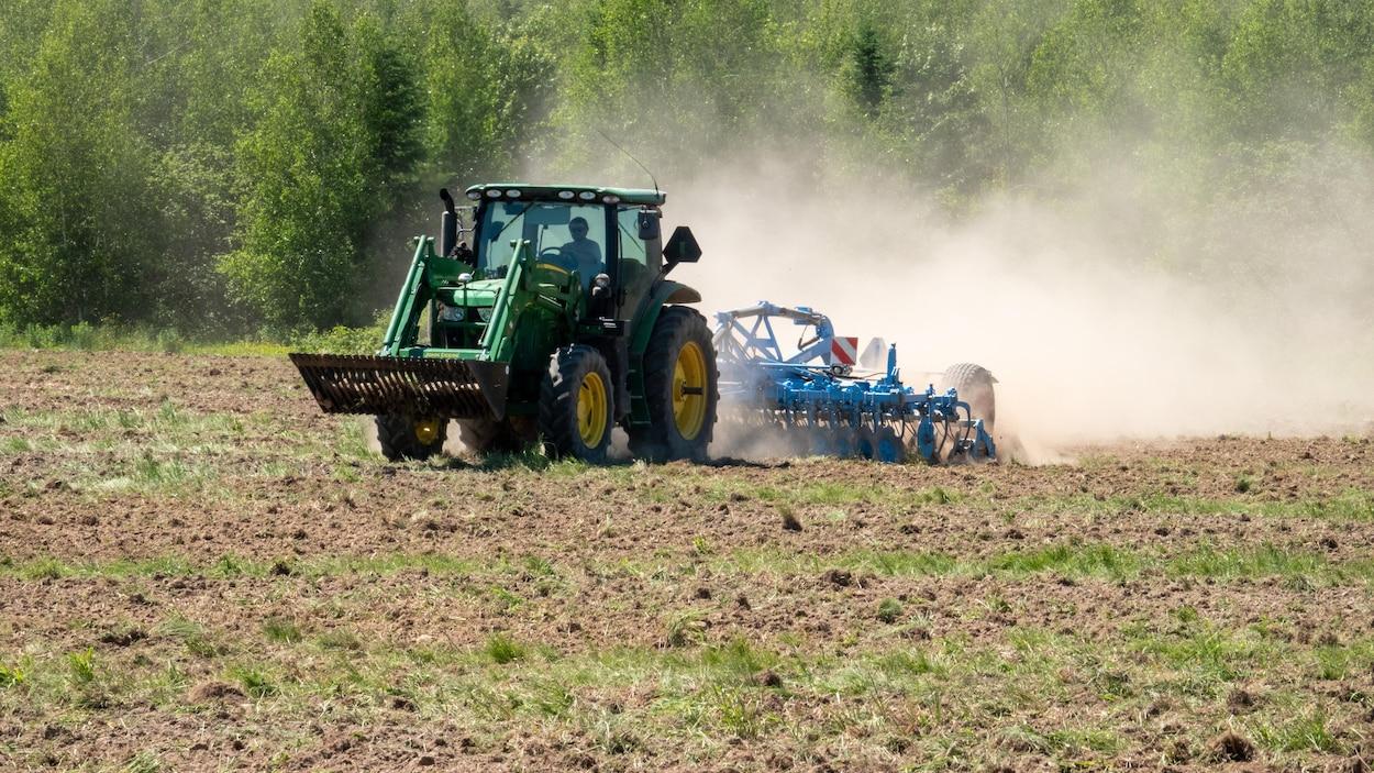 Un cultivateur sur un tracteur dans un champ.