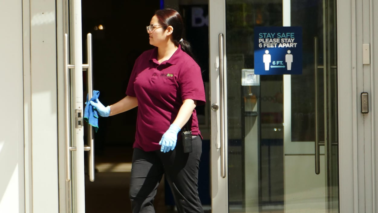 Une employée essuie les poignées de porte.