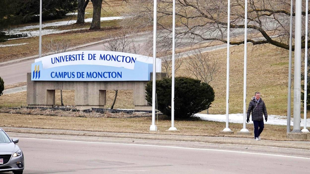 Une passante devant l'enseigne du campus de Moncton.