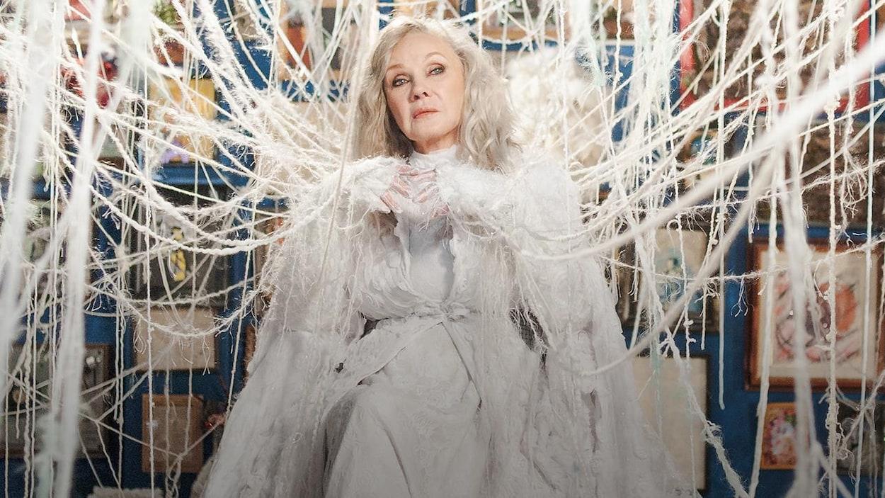 L'artiste pose au centre d'une pièce, attachée à d'innombrables ficelles.