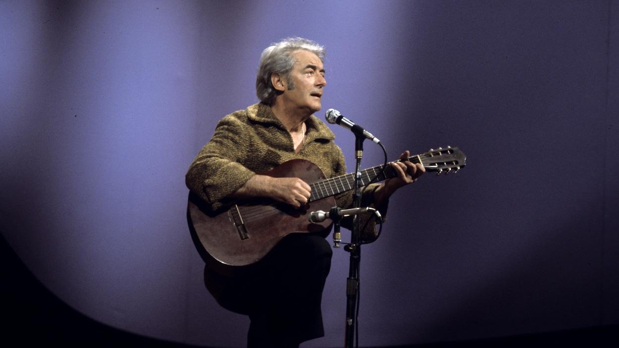 Dans un studio de télévision, le chanteur Félix Leclerc, chante en s'accompagnant de sa guitare devant un micro sur pied