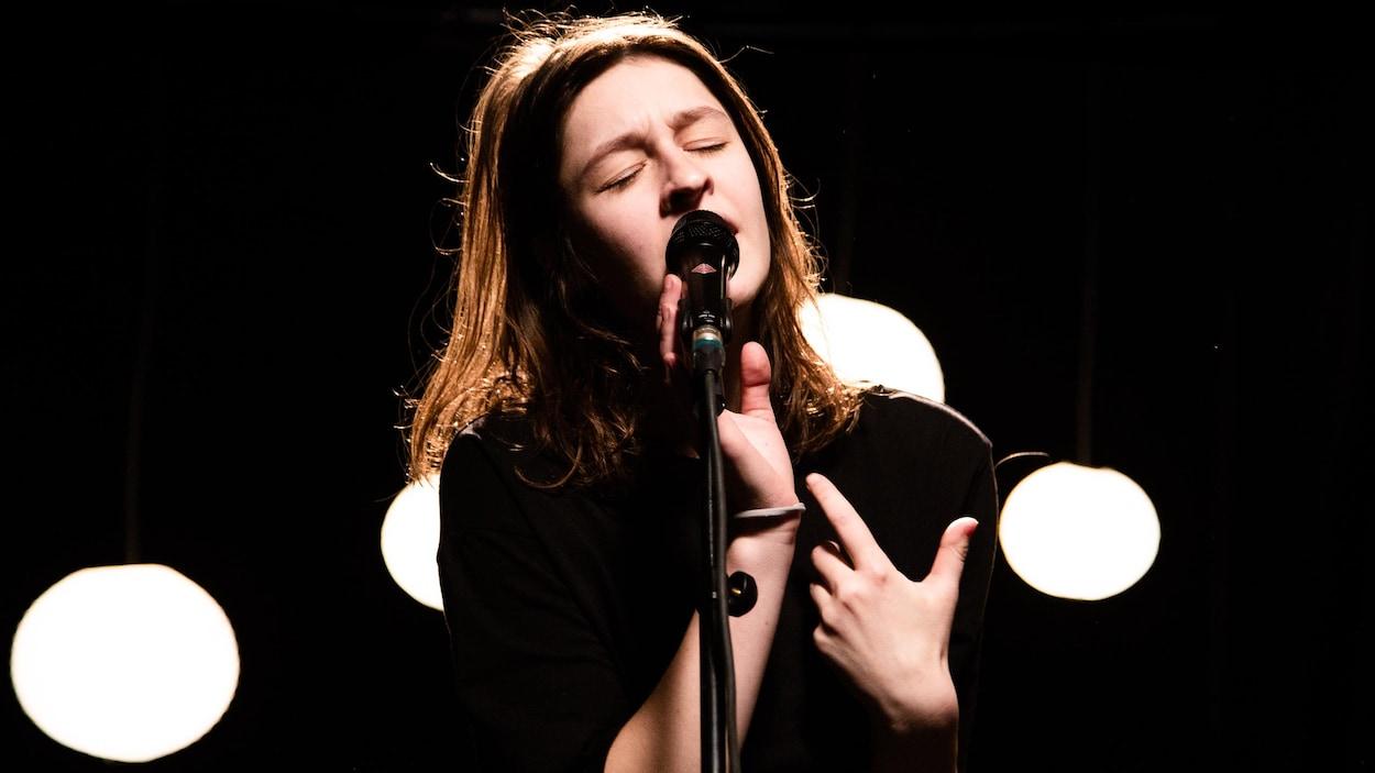 La jeune artiste Lou-Adriane Cassidy chante, avec émotions et les yeux fermés, sa chanson Poussière dans les studios de Radio-Canada.