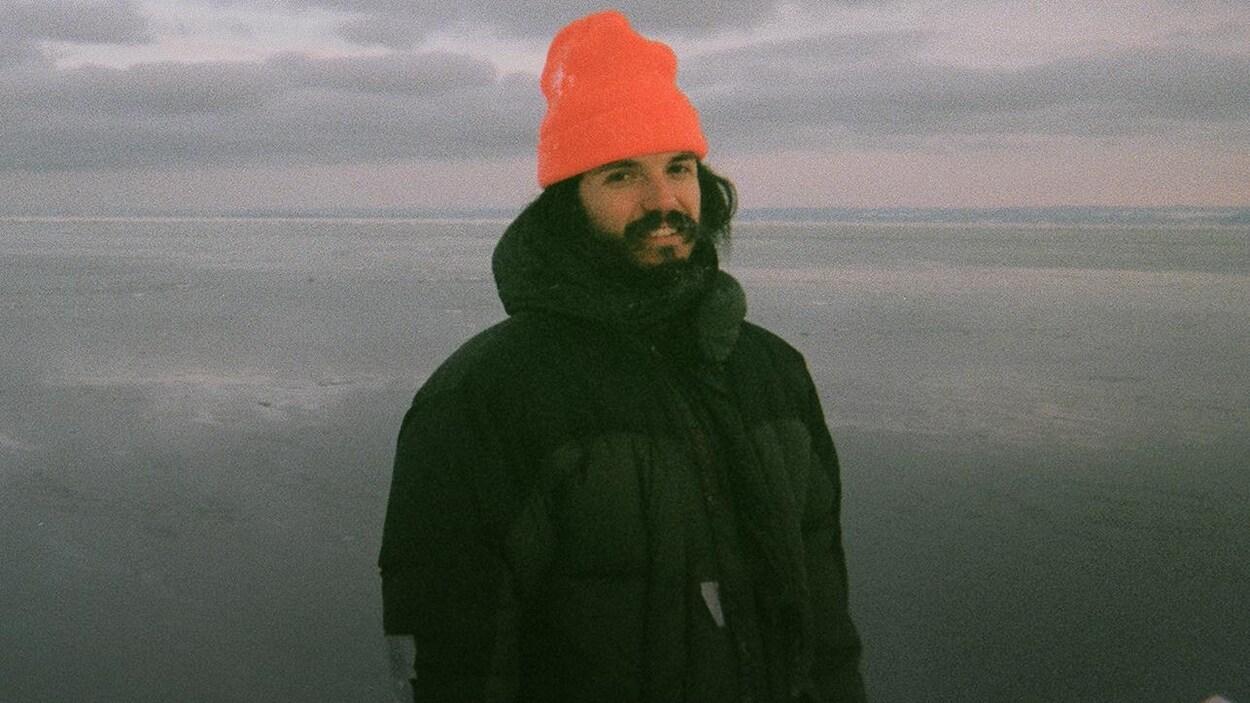 Philémon Cimon devant une vaste étendue d'eau en hiver.