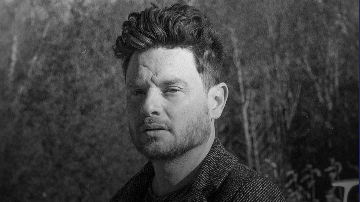 Un portrait noir et blanc du chanteur Yann Perreau, vu de profil.