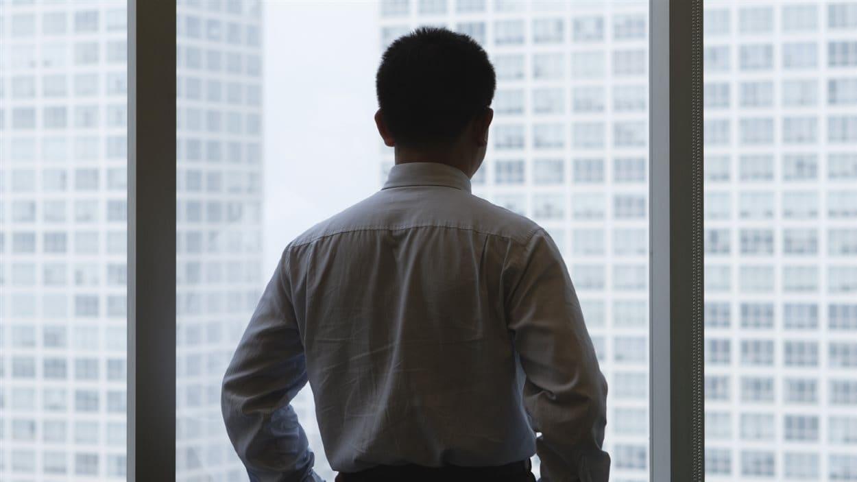Un homme regarde par la fenêtre de son bureau.