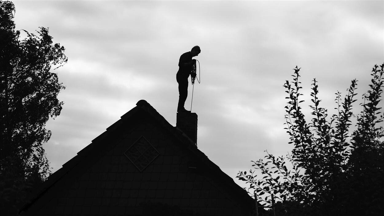 Un ramoneur sur le toit d'une maison.