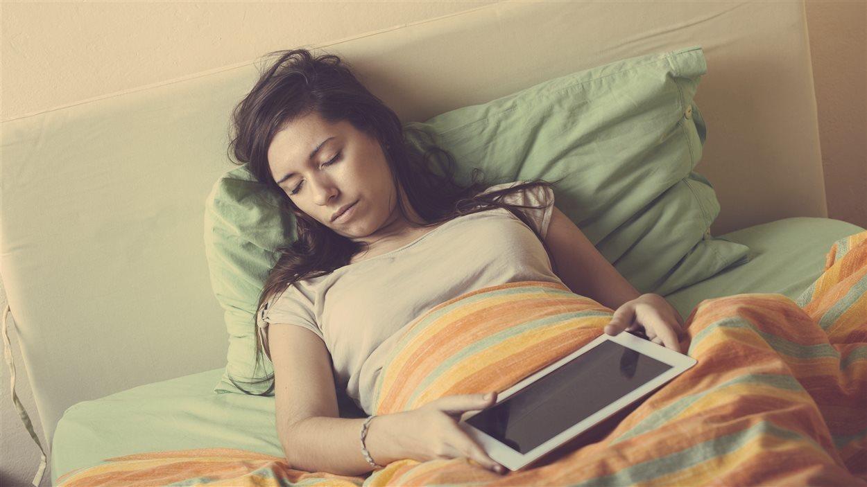 Une femme en train de dormir au lit.