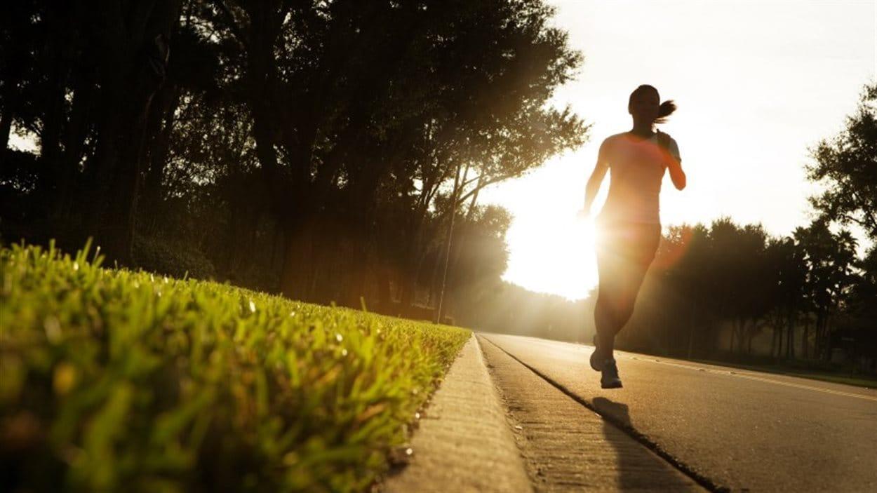 Une femme court au levé du soleil