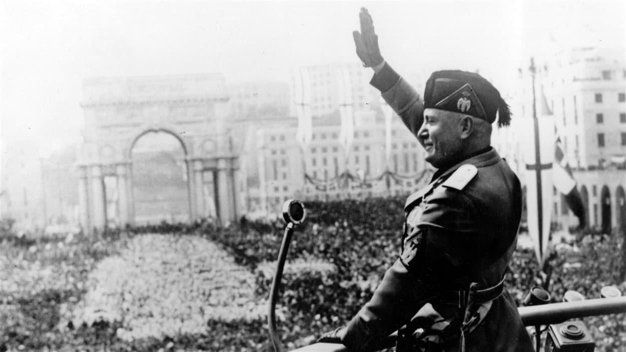Le dictateur italien Benito Mussolini donne un discours du haut d'un balcon devant une très grande foule.
