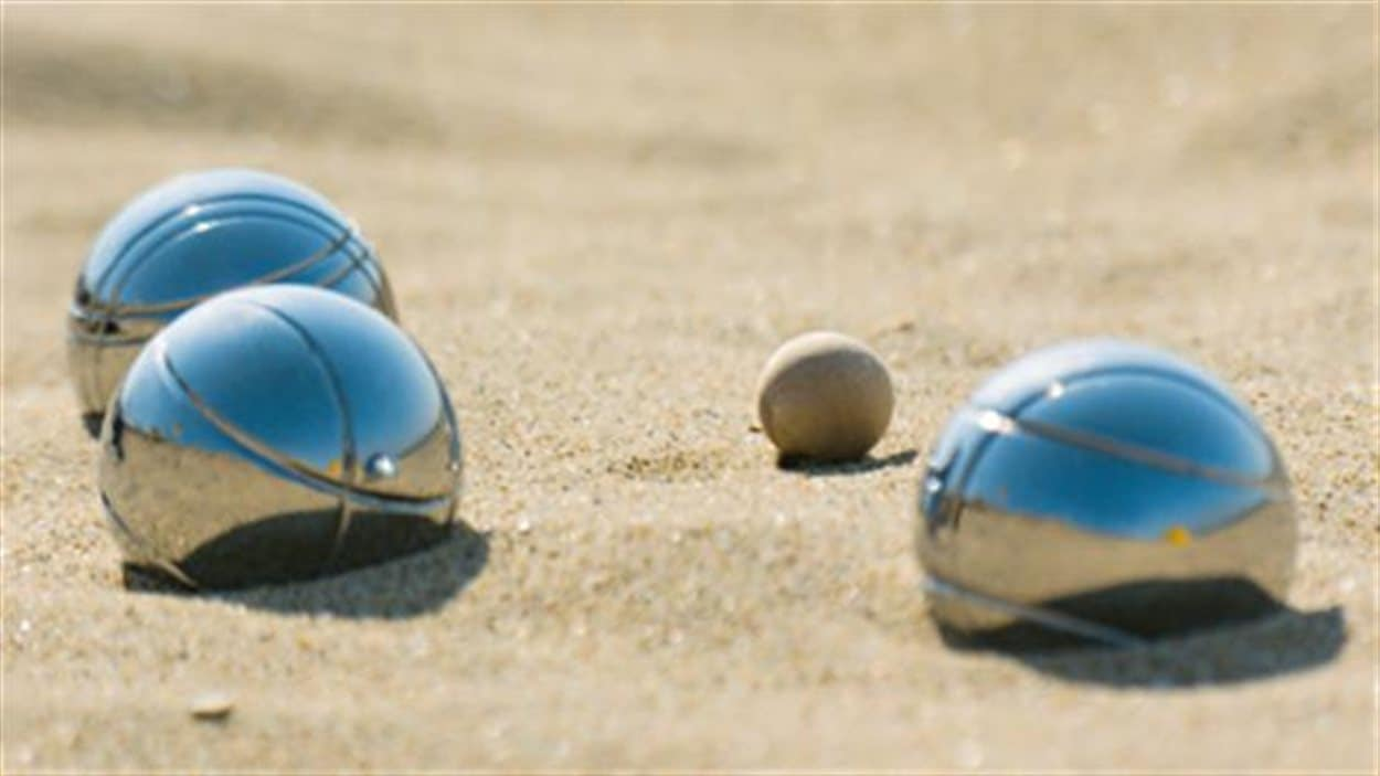 Des boules de pétanque dans le sable.