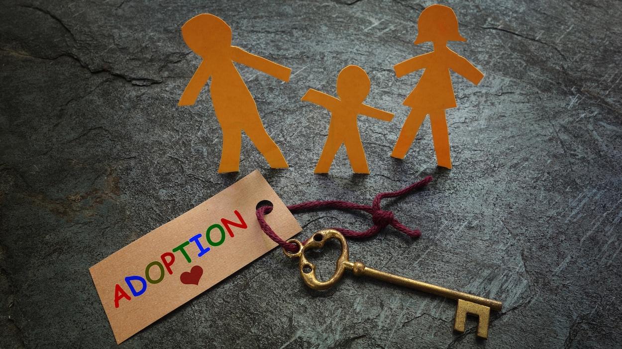 Représentation d'une famille en figurines de papier, placées tout près d'une clé de maison familiale et d'une étiquette portant la mention Adoption.
