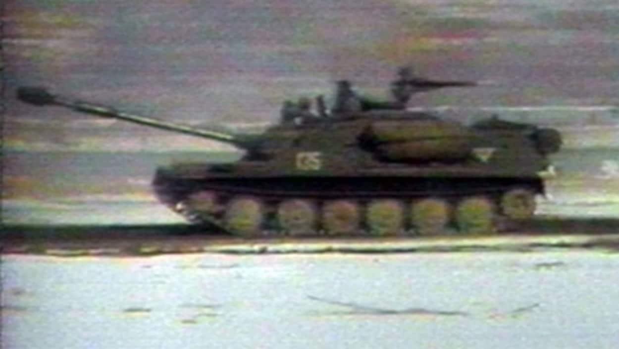 On voit une image floue d'un blindé soviétique patrouillant en terrain afghan.
