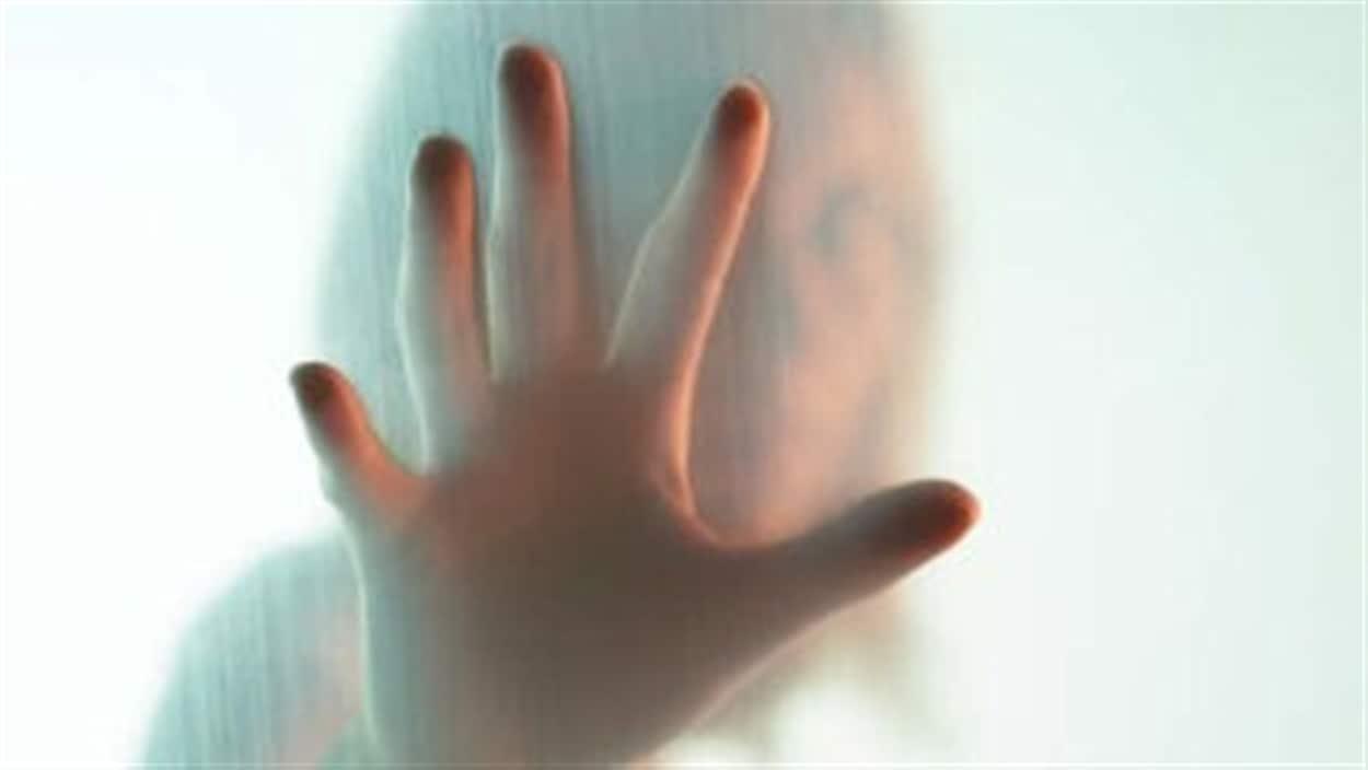 La main d'une femme sur une vitre embuée.