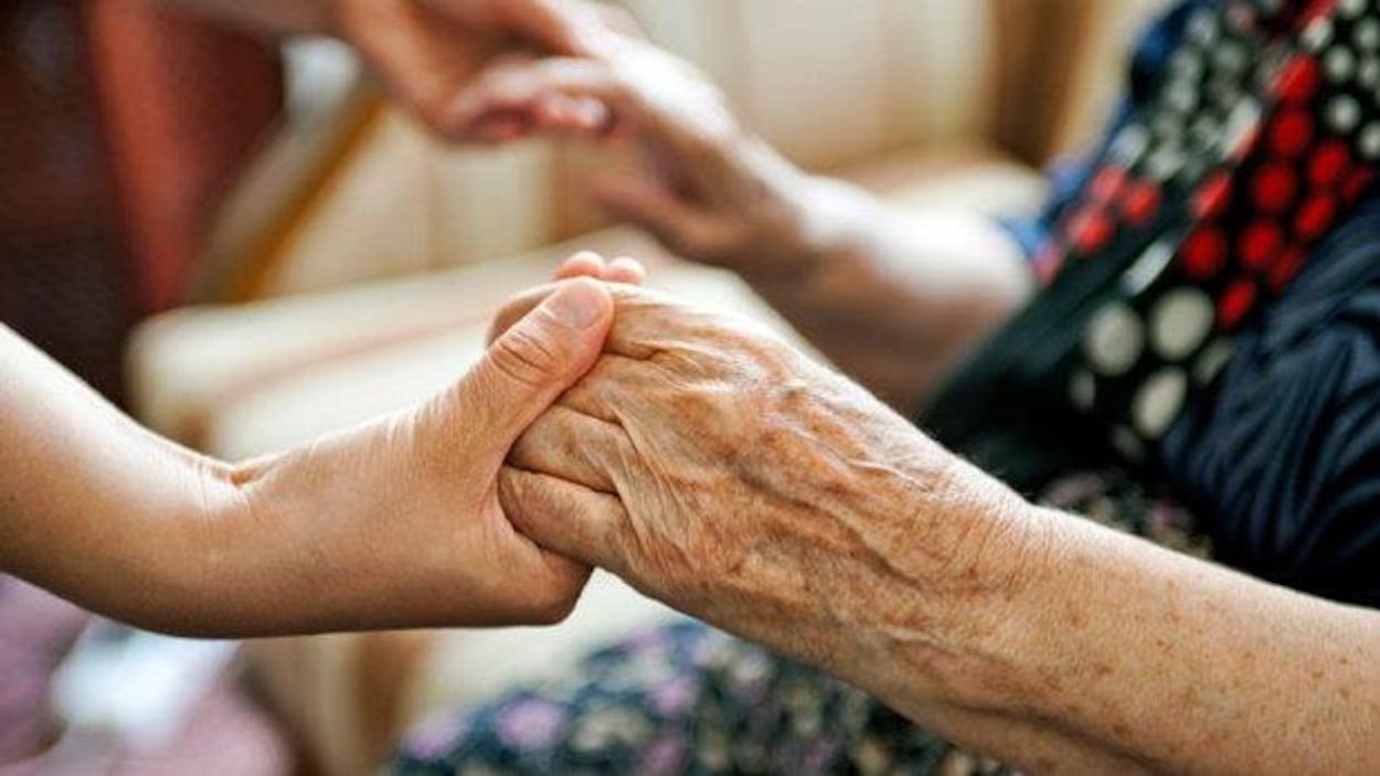 Plan serré des mains d'une jeune personne qui tient les mains d'une personne âgée.