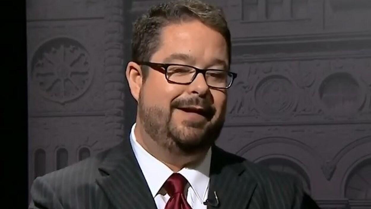 Un homme barbu portant des lunettes.