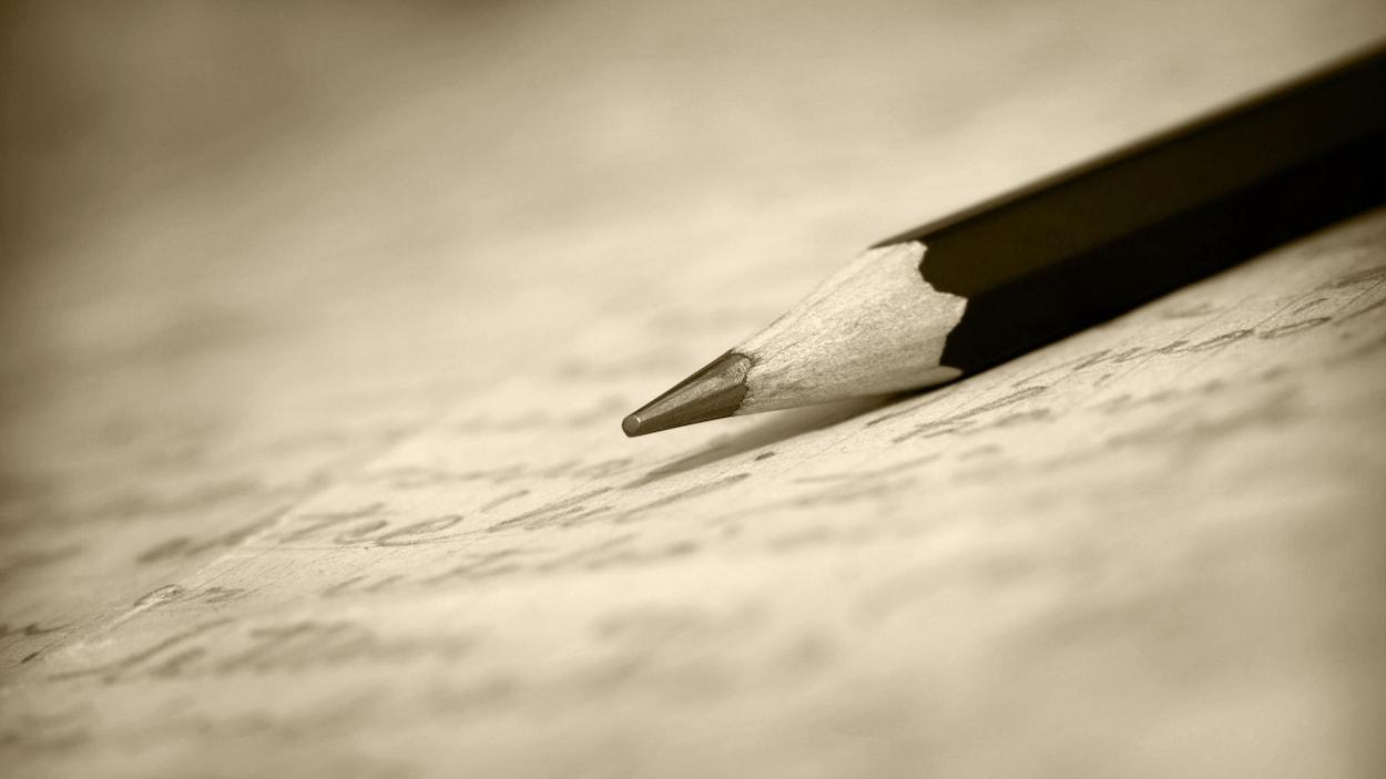 Un crayon déposé sur une feuille de papier remplie d'écritures.