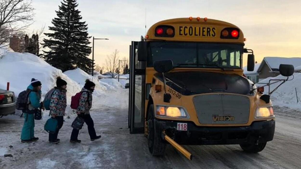 En banlieue l'hiver, trois enfants montent à bord d'un autobus scolaire.
