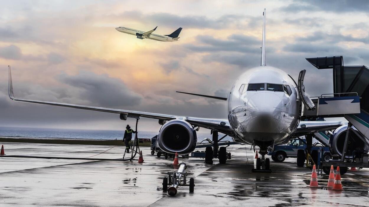 Un avion est sur le tarmac d'un aéroport pendant qu'un autre décolle.