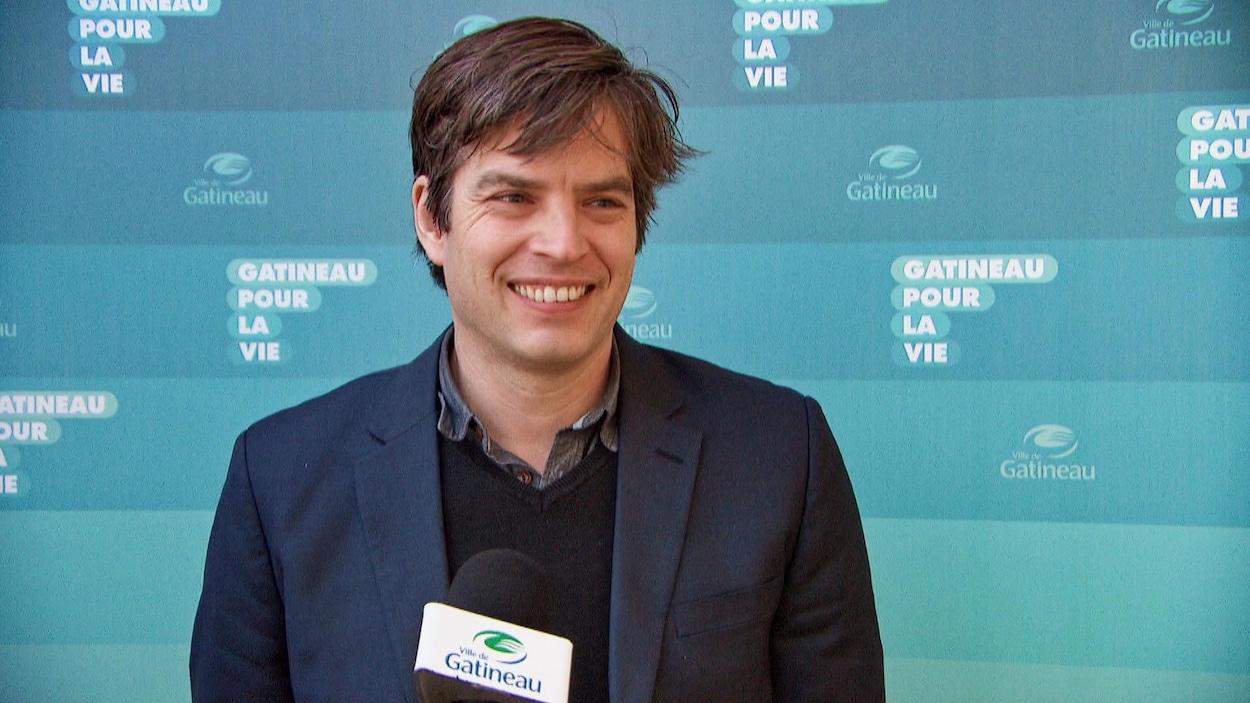 Benoit Dellage en entrevue devant un fond bleu portant l'inscription : Gatineau pour la vie.