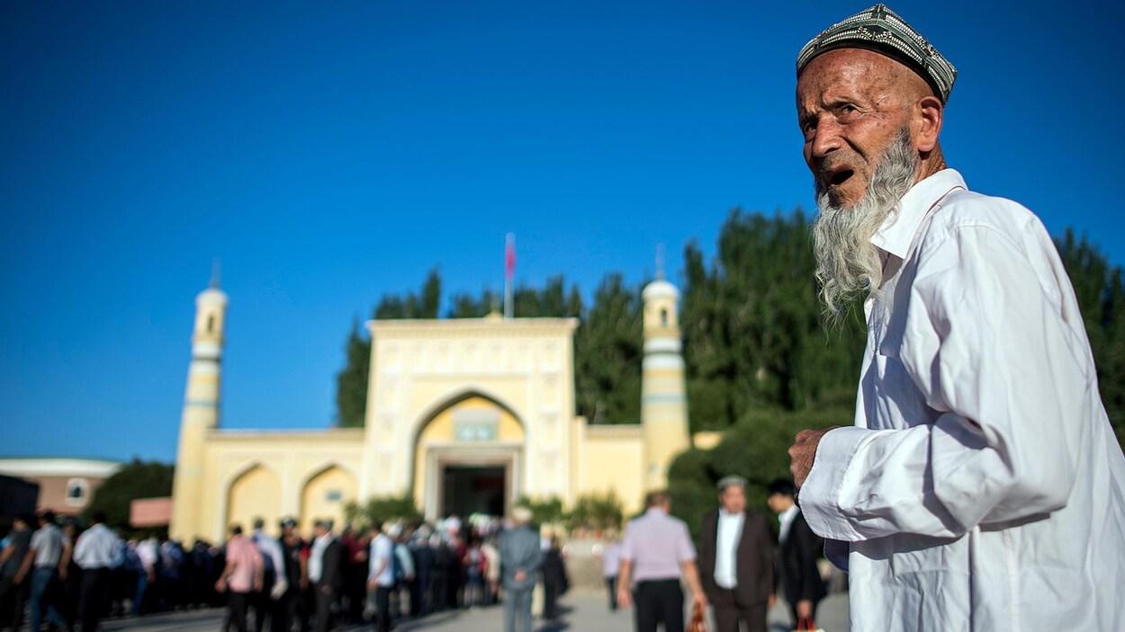 En avant-plan, un homme est devant une mosquée; plusieurs personnes sont massées devant la mosquée.