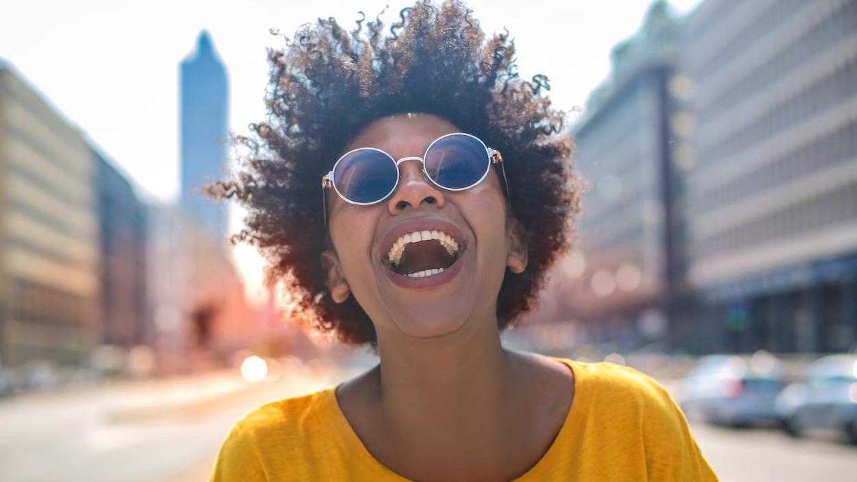 Une jeune femme avec des lunettes soleil sourit à grandes dents.