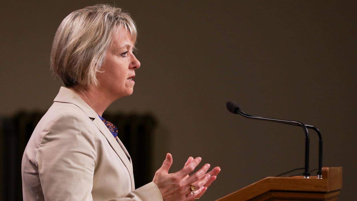 Bonnie Henry est debout devant un micro dans une salle devant un auditoire.