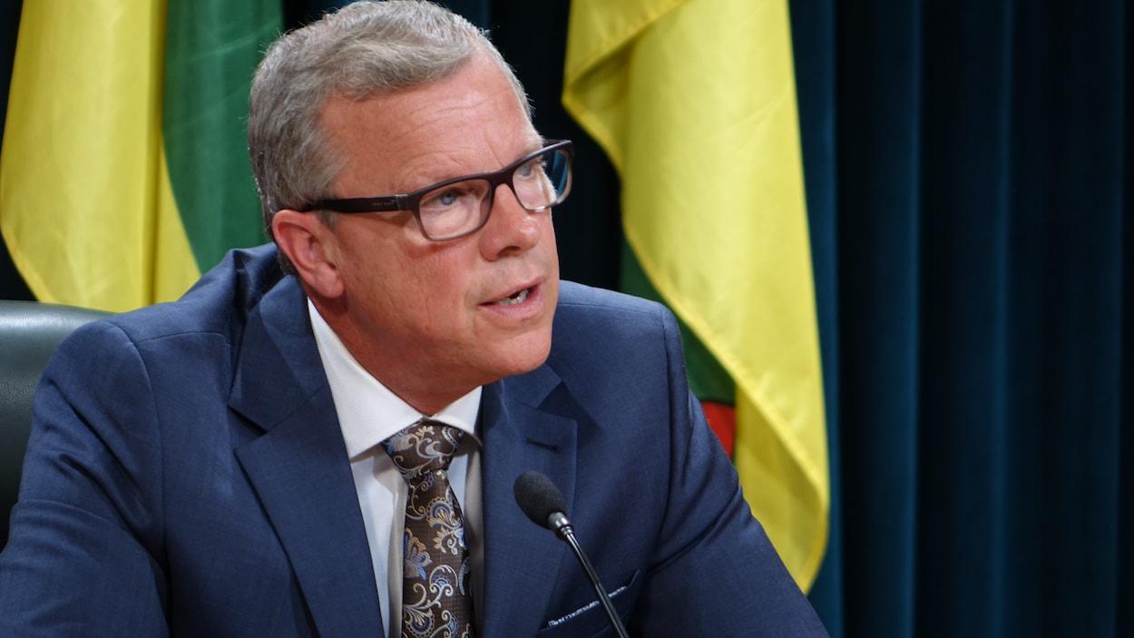 Le premier ministre de la Saskatchewan, Brad Wall, devant le drapeau de la province.