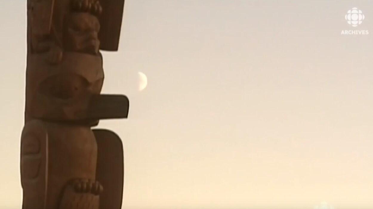 La lune brille à côté d'un totem en Colombie-Britannique.